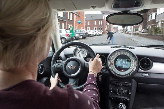 Foto waarbij over de schouder van een mevrouw meegekeken wordt hoe ze een straat in rijdt waar kinderen op straat aan het spelen zijn