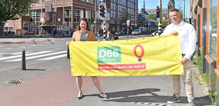 2 vertegenwoordigers van D66 geven met een spandoek aan een punt van nul te maken.