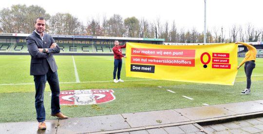"""Twee mensen van FC Dordrecht houden een spandoek vast met """"Hier maken wij een punt van nul verkeersslachtoffers - doe mee"""""""