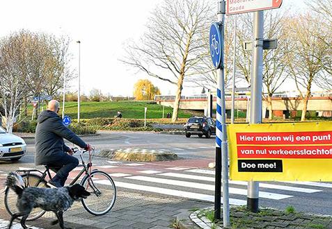 Een fietser in de gemeente Zuidplas bekijkt een spandoek van Maak Een Punt Van Nul