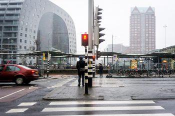 Straatbeeld van Rotterdam. Een man wacht voor een verkeerslicht.