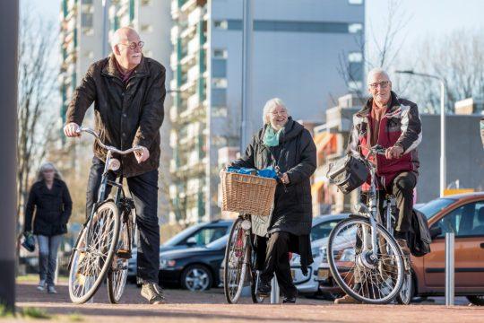 Foto van drie senioren die veilig staan te wachten op de stoep met hun fietsen in de hand.
