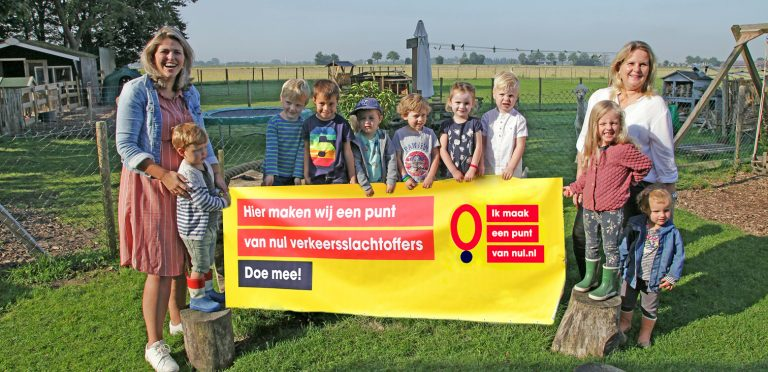 """Kinderen van de Peuterhoeve houden een spandoek vast met """"Hier maken wij een punt van nul verkeersslachtoffers - doe mee"""""""
