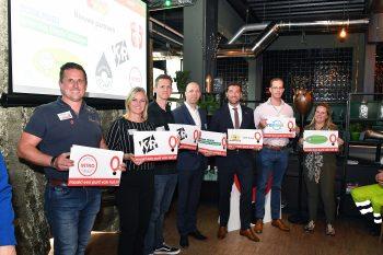 Vertegenwoordigers bij een verkeersveiligheidsymposium. Logo's van deelnemende bedrijven worden getoond die een Punt Van Nul maken.