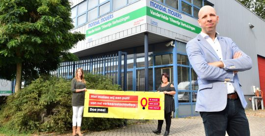 """Twee mensen van Van der Velde houden een spandoek vast met """"Hier maken wij een punt van nul verkeersslachtoffers - doe mee"""""""