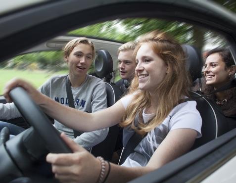 Groep jongeren in een auto waarbij het belang wordt gelegd op aandacht op de weg houden.