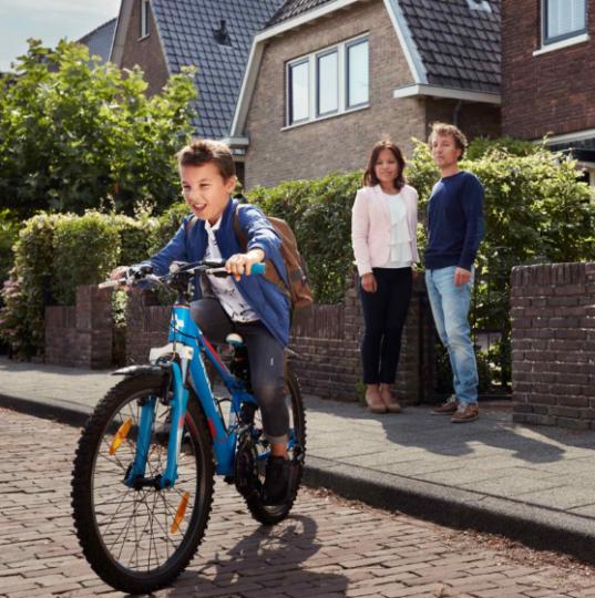 Twee ouders staan voor het huis te kijken naar hun zoontje die weg fietst op zijn blauwe fiets