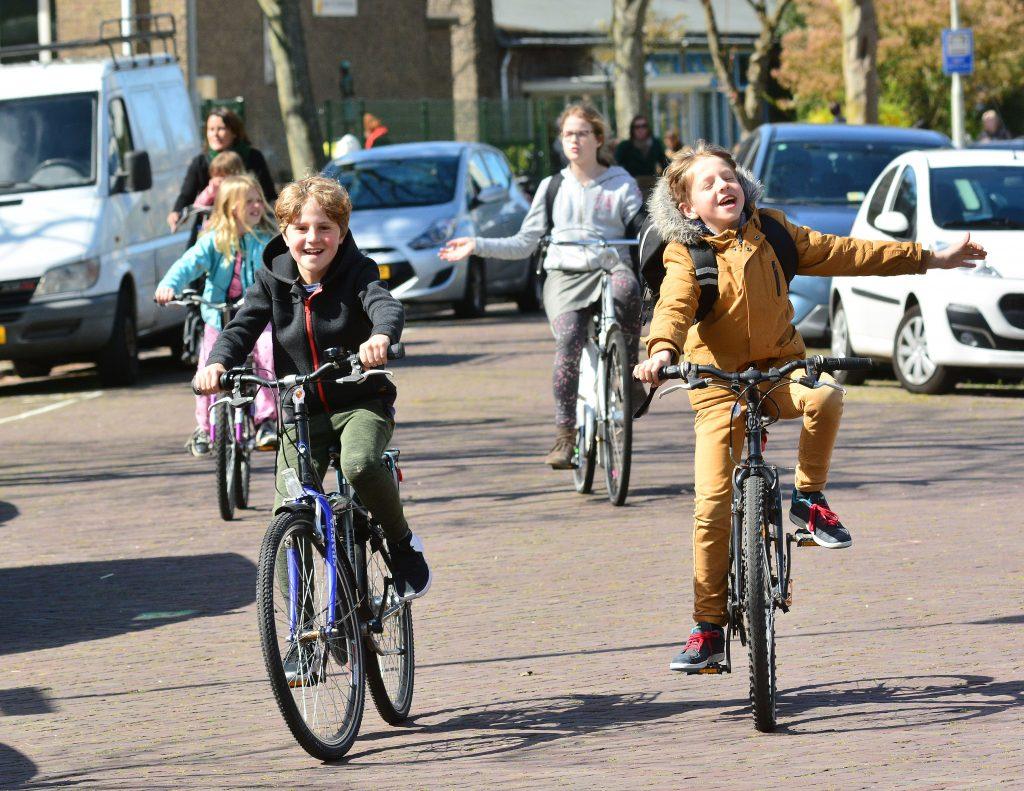4 blije fietsende kinderen op straat.