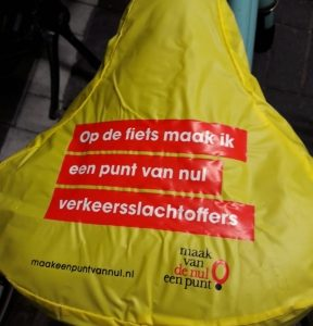 Foto van een geel zadelhoesje. De opdruk luidt: Op de fiets maak ik een punt van nul verkeersslachtoffers.