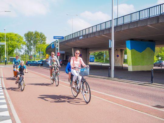 Twee moeders en een vader fietsen met hun kinderen achterop langs onder de brug.
